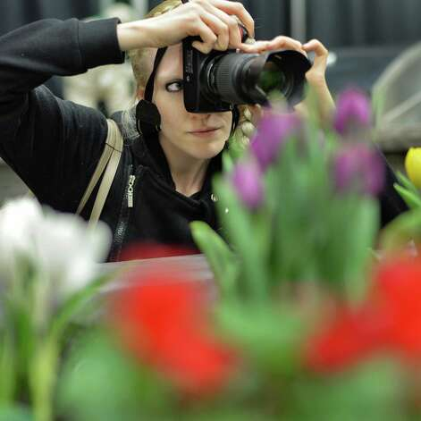 Erika Bjork of Tampa, Florida focuses in on some spring color during the Capital District Garden & Flower Show at HVCC Friday March 27, 2015 in Troy, NY.  (John Carl D'Annibale / Times Union) Photo: John Carl D'Annibale / 00031205A