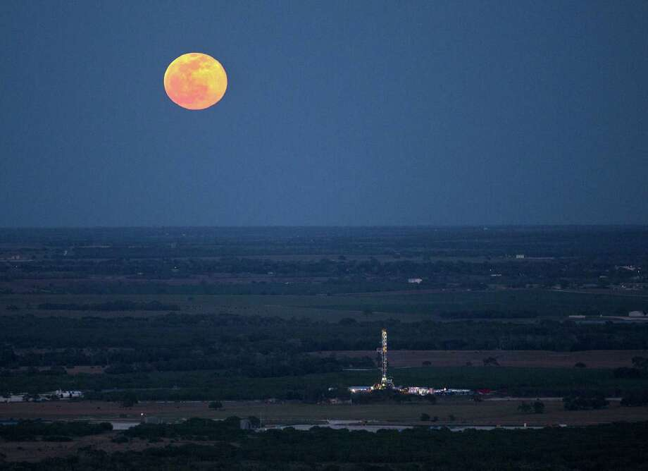 The full moon rises above an oil drilling rig near Karnes City. Karnes County wells have the highest estimated ultimate recovery in the Eagle Ford. Photo: Express-News File Photo / © 2014 San Antonio Express-News
