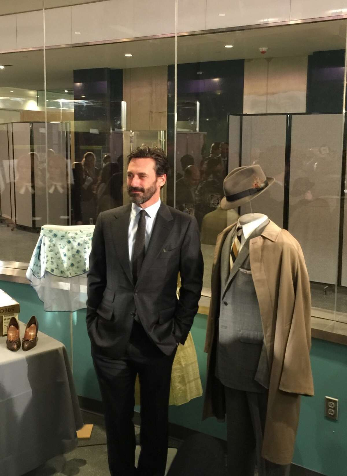 Actor Hamm poses next to one of his signature Don Draper suits.