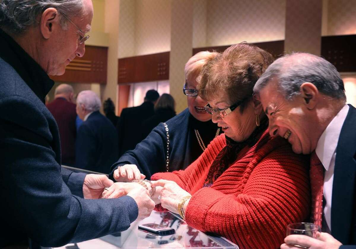 Virginia Fortin, a benefactor of St. Vincent's Swim Across the Sound and volunteer, tries on a bracelet provided by vendor David Spivak at Madison Jewelers in Fairfield during
