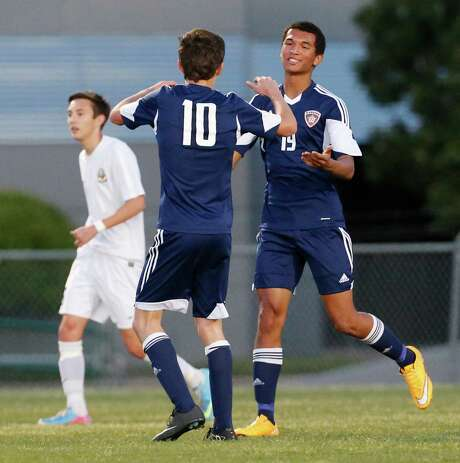 Smithson Valley's Andrew Beard (19) gets congratulated by teammate Luis Green (10) after scoring the team's second goal against MacArthur in Class 6A boys soccer playoffs at Blossom West on March 27, 2015. Photo: Kin Man Hui /San Antonio Express-News / ©2015 San Antonio Express-News