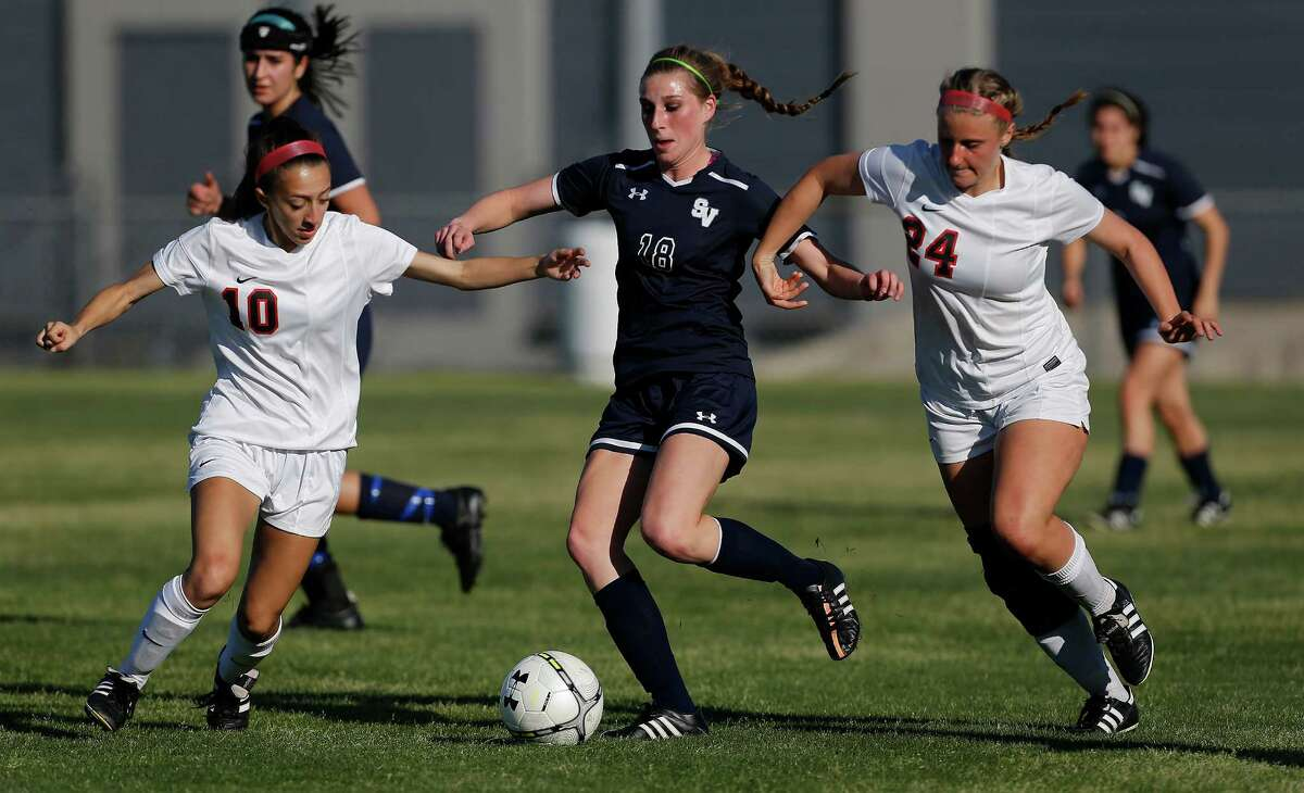 Smithson Valley's Brooke Cousins (center) fends off Churchill's Claudia Mendoza (left) and Claire Treu (right) in the Class 6A girls soccer playoffs at Blossom West Stadium on March 27, 2015. Cousins kicked the last-second winning goal to seal a victory for Smithson Valley.