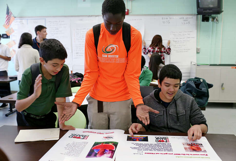 Thomas Benavidez, 14 (from left), Marquaveon Cabness, 14, and Juan Rodriguez, 15, congratulate each after finishing posters promoting a school farmers market. Photo: Jerry Lara /San Antonio Express-News / © 2015 San Antonio Express-News