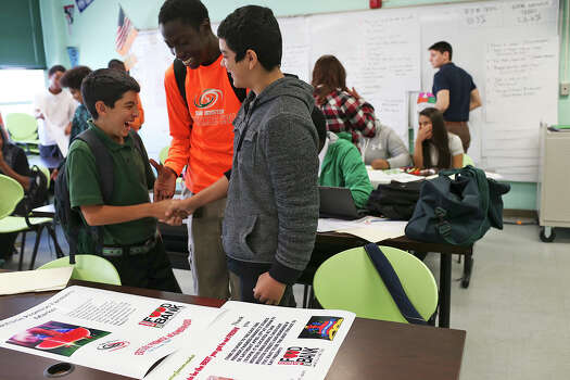 From left, Thomas Benavidez, 14, Marquaveon Cabness, 14, and Juan Rodriguez, 15, congratulate each other as they look at posters designed by them promoting a school farmers market. Photo: Jerry Lara /San Antonio Express-News / © 2015 San Antonio Express-News