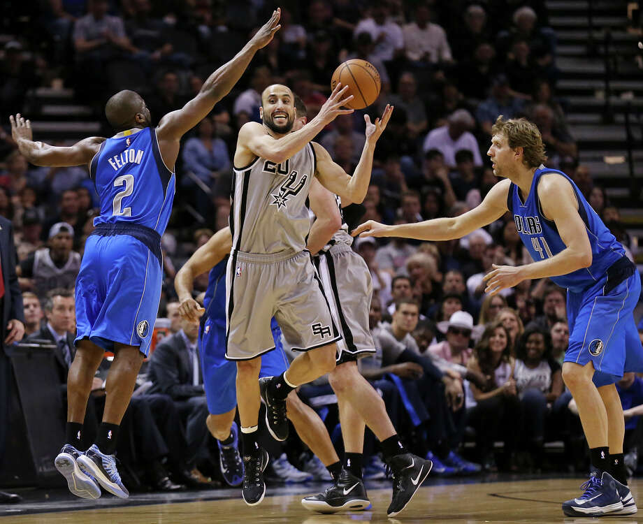 San Antonio Spurs' Manu Ginobili looks for room between Dallas Mavericks' Raymond Felton (left) and Dirk Nowitzki during first half action Friday March 27, 2015 at the AT&T Center. Photo: Edward A. Ornelas, Staff / San Antonio Express-News / © 2015 San Antonio Express-News