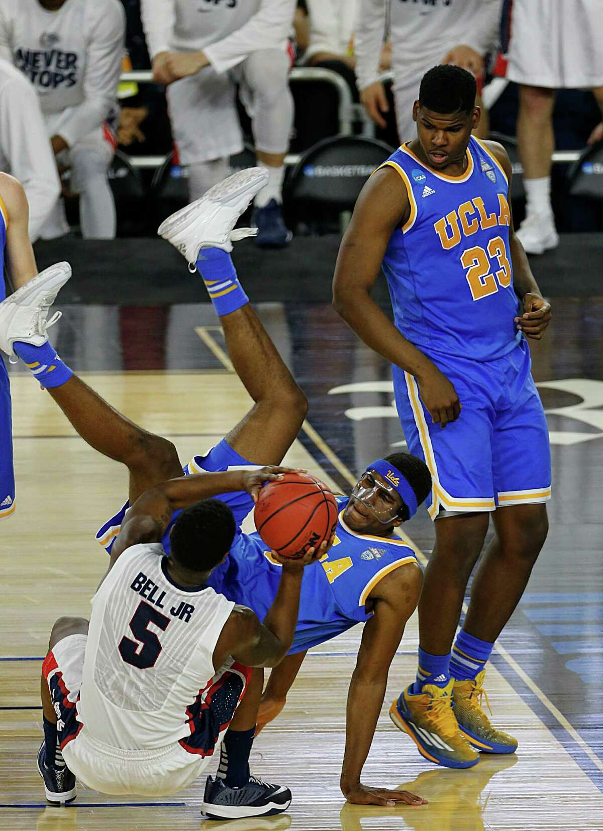 UCLA Bruins forward Kevon Looney center, falls onto Gonzaga Bulldogs guard Gary Bell Jr. left, as UCLA's Tony Parker right, looks on during the second half of the NCAA South Regional semifinal game at NRG Stadium Friday, March 27, 2015, in Houston. ( James Nielsen / Houston Chronicle )