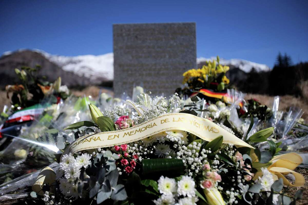 A stele and flowers laid in memory of the victims are placed in the area where the Germanwings jetliner crashed in the French Alps, in Le Vernet, France, Friday, March 27, 2015. The crash of Germanwings Flight 9525 into an Alpine mountain, which killed all 150 people aboard, has raised questions about the mental state of the co-pilot. Authorities believe the 27-year-old German deliberately sought to destroy the Airbus A320 as it flew Tuesday from Barcelona to Duesseldorf. (AP Photo/Christophe Ena) ORG XMIT: ENA101