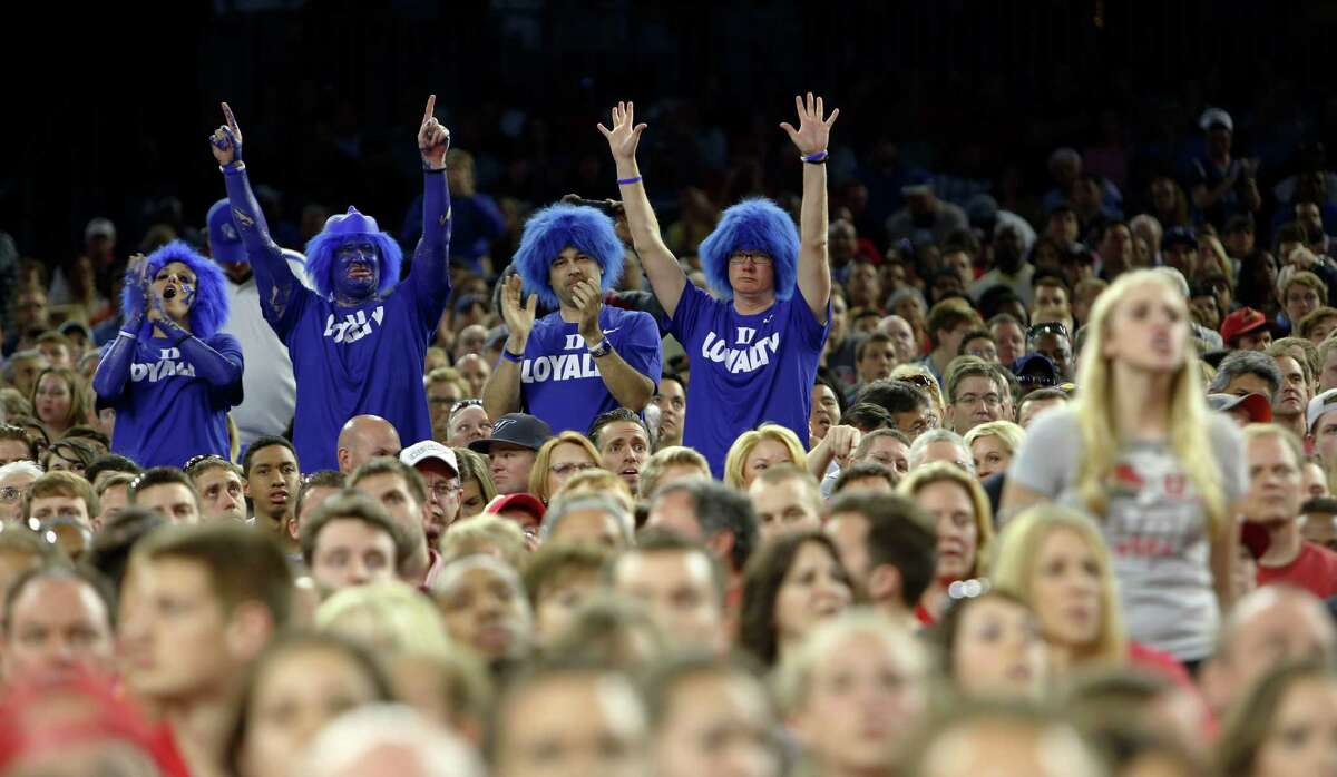 A group of Duke fans celebrate a play during the first half of the NCAA South Regional semifinal game between Duke and Utah Friday, March 27, 2015, in Houston.