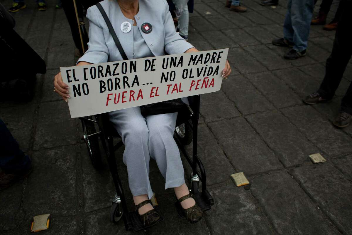 """A woman holds a sign that reads in Spanish, """"The heart of a mother doesn't erase ... doesn't forget. Out with so-called Peña,"""" referring to Mexico President Enrique Peña Nieto."""