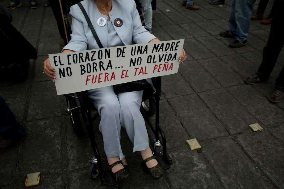 "A woman holds a sign that reads in Spanish, ""The heart of a mother doesn't erase … doesn't forget. Out with so-called Peña,"" referring to Mexico President Enrique Peña Nieto. Photo: Rebecca Blackwell, STF / AP"