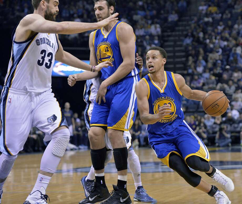 Golden State Warriors guard Stephen Curry, right, gets assistance from Warriors center Andrew Bogut (12) as he drives against Memphis Grizzlies center Marc Gasol (33) and guard Mike Conley in the first half of an NBA basketball game Friday, March 27, 2015, in Memphis, Tenn. (AP Photo/Brandon Dill) Photo: Brandon Dill, Associated Press