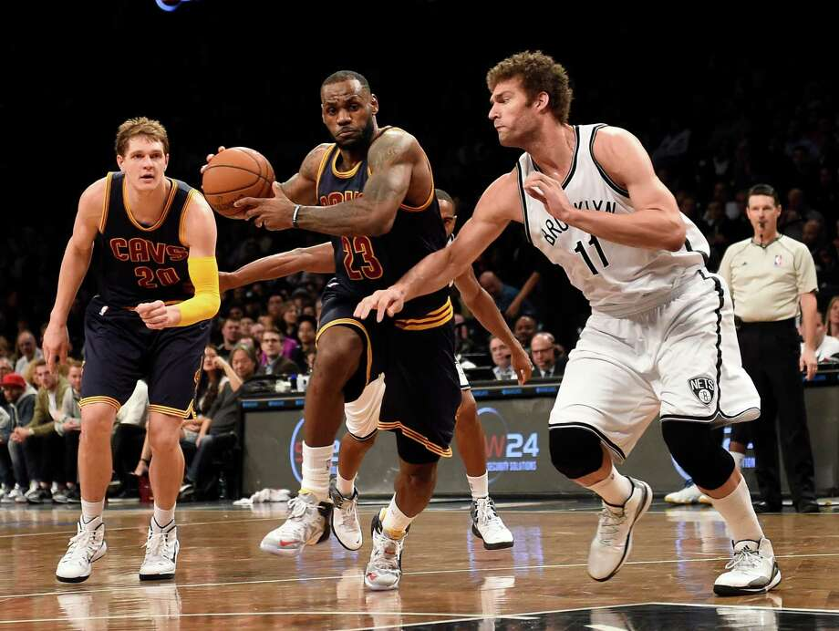 Cleveland Cavaliers forward LeBron James (23) drives the ball around Brooklyn Nets center Brook Lopez (11) as Cavaliers center Timofey Mozgov (20) defends from behind in the first half of an NBA basketball game on Friday, March 27, 2015, in New York. The Nets won 106-98. (AP Photo/Kathy Kmonicek) ORG XMIT: NYKK114 Photo: Kathy Kmonicek / FR170189 AP