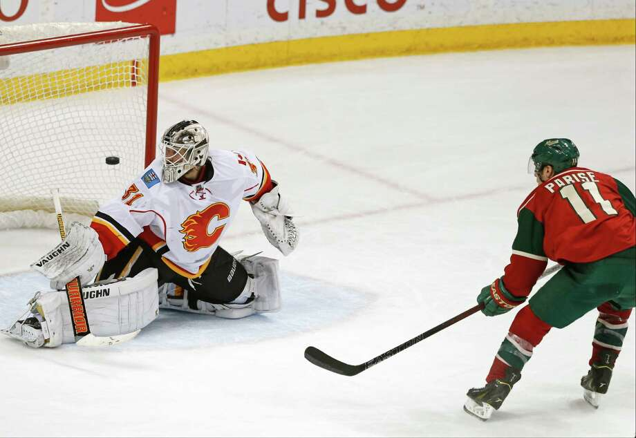 Minnesota Wild's Zach Parise, right, scores against Calgary Flames goalie Karri Ramo, of Finland, in the third period of an NHL hockey game Friday, March 27, 2015, in St. Paul, Minn. The Wild won 4-2. (AP Photo/Jim Mone) ORG XMIT: MNJM108 Photo: Jim Mone / AP