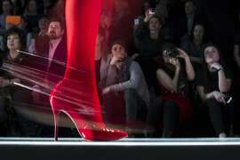 Spectators watch as a model displays a creation by Russian designer Slava Zaitsev during Fashion Week, in Moscow, Russia, Friday, March 27, 2015. (AP Photo/Pavel Golovkin)