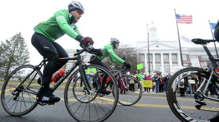 "At left, Team 26 member, Matt Emeott of Lutherville, Md., rides up to the Greenwich Council Against Gun Violence annual rally in support of ""Team 26"" (26 cyclists) who are pedaling 400 miles from Sandy Hook, Conn., to Washington, D.C., to raise awareness for common-sense gun safety laws and to honor victims of gun violence during the team's stop at Greenwich Town Hall, Conn., Saturday, March 28, 2015."