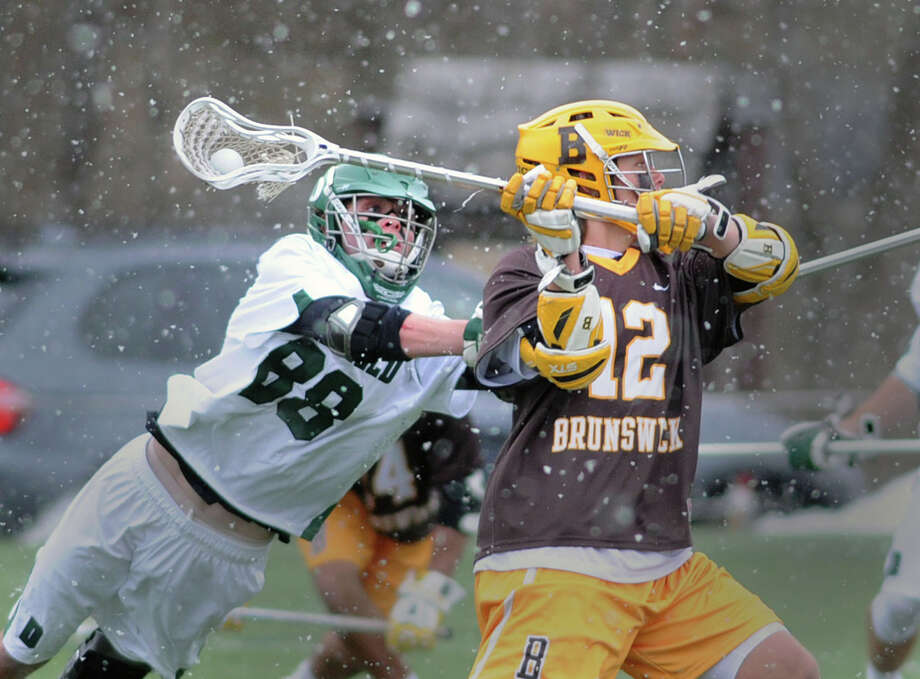 Deerfield's Matt Kane (#88), left, dives in an attempt to prevent a shot by Brunswick's Jack Knight (#12), at right, as a spring snow shower made playing conditions difficult during the boys high school lacrosse game between Brunswick School and Deerfield Academy at Brunswick School in Greenwich, Conn., Saturday, March 28, 2015. Photo: Bob Luckey / Greenwich Time