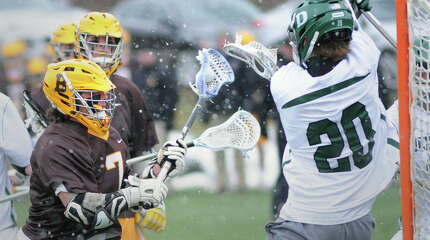 As his Brunswick teammate Tucker Brown looks on from behind, Alex Buckanavage (#7), left, scores a goal past Philip Goss, the Deerfield goalie during the boys high school lacrosse game between Brunswick School and Deerfield Academy at Brunswick School in Greenwich, Conn., Saturday, March 28, 2015.