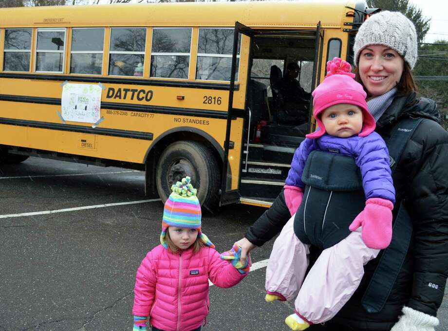 The Kellehers, Hannah, 2, and baby Bridget, 9 months, get a first taste of riding the school bus, along with mom Keri Kelleher at Saturday's Touch-a-Truck event sponsored by the Westport Weston Cooperative Nursery School. Photo: Jarret Liotta / Westport News