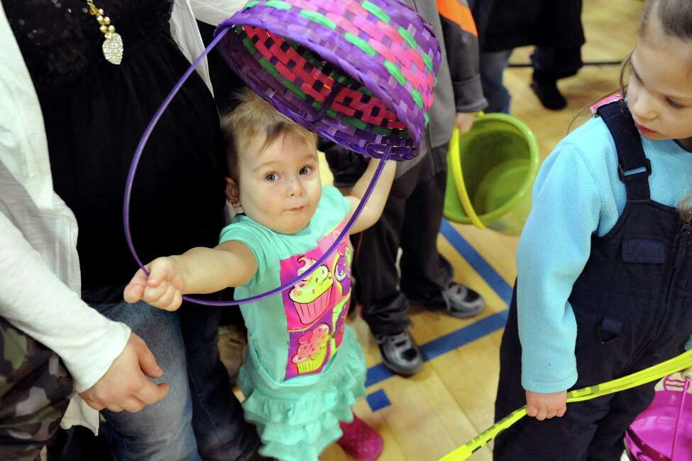 Jocelyn Semenske, 2, center, of Cohoes plays with her Easter basket while waiting for the start of the Annual Cohoes Easter Egg Hunt on Saturday, March 28, 2015, at Cohoes Community Center in Cohoes, N.Y. (Cindy Schultz / Times Union)