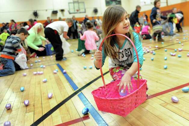 April Garneau, 5, right, of Cohoes picks up plastic eggs filled with candy or tickets for prizes during the Annual Cohoes Easter Egg Hunt on Saturday, March 28, 2015, at Cohoes Community Center in Cohoes, N.Y. (Cindy Schultz / Times Union) Photo: Cindy Schultz / 00031212A