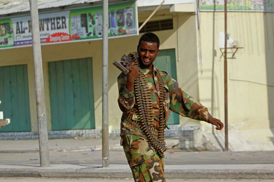 A Somali soldier takes position during fighting with militants who were inside a hotel in Mogadishu, Somalia, on Saturday. Somali troops took full control of the hotel later Saturday. Photo: Farah Abdi Warsameh, STR / AP