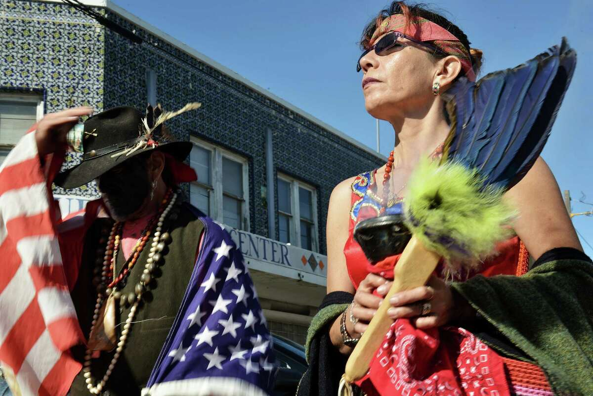 Barbara Hernandez (right), related to the Lakota Sioux tribe, and John a del Pozo, related to the Mascalero Apache tribe, do a ceremonial blessing at the start of the annual César Chávez March for Justice from the West Side to the Alamo.