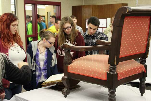 Ravena-Coemans-Selkirk students look over a chair that President Abraham Lincoln sat in at the War Department (today?s Old Federal Building) when he awaited the telegraph that said he had won re-election in 1864. It was originally owned by Gideon Wells, U.S. Secretary of the Navy from 1861 to 1869. The occasion was a commemoration at the school on Thursday of the 150th anniversary of the end of the Civil War. (Submitted by Sabre Sarnataro)