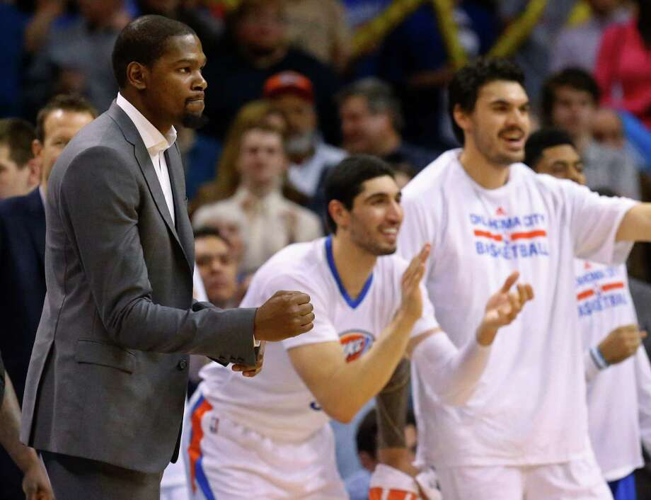 FILE - In this March 8, 2015, file photo, injured Oklahoma City Thunder forward Kevin Durant, left, pumps his fist as teammates Enes Kanter, center, and Steven Adams, right, cheer during the fourth quarter of an NBA basketball game against the Toronto Raptors in Oklahoma City. Durant will have bone graft surgery next week to deal with a fractured bone in his right foot, and he will miss the rest of the season, the Oklahoma City Thunder announced Friday, March 27, 2015.  (AP Photo/Sue Ogrocki, File) Photo: Sue Ogrocki, STF / Associated Press / AP