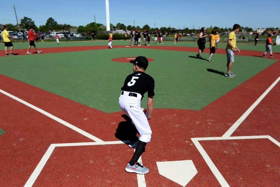 Zachary Portzline, 12, a Miracle League baseball player, gets ready to run the bases of the new J.E. & L.E. Mabee Adaptive Sports Complex on Saturday. Photo: Gary Coronado, Staff / © 2015 Houston Chronicle