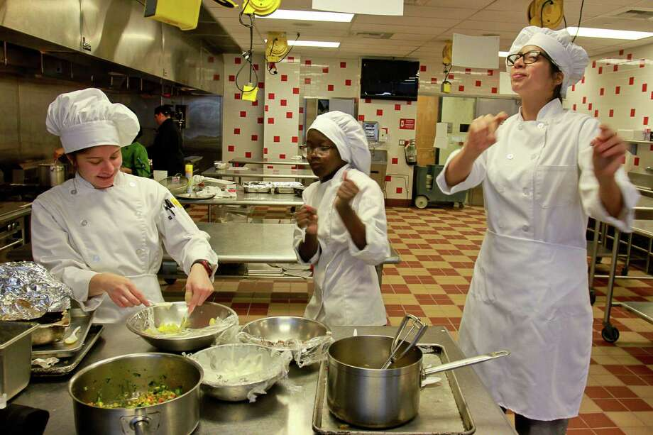 Alexa Guerrero, from left, Ta'Mirah Collins and Kassandra Cias of Barbara Jordan High School Team 2,dance after making their presentation to the judges for Cooking Up Change, a healthy cooking competition. Photo: Gary Fountain, Freelance / Copyright 2015 by Gary Fountain