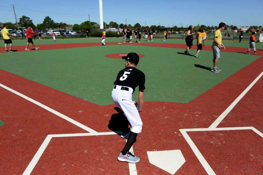 Zachary Portzline, 12, a Miracle League baseball player, prepares to run the bases at the grand opening of the J.E. & L.E. Mabee Adaptive Sports Complex at the Langham Creek Family YMCA Saturday, March 28, 2015, in Houston, Texas. The $2.4 million facility consists of an artificial turf baseball field, a covered multipurpose pavilion, a barrier-free playground, to be built later, and a lush green space at its center. The baseball field will be home to the Miracle League, a youth baseball program dedicated  to children with physical and mental disabilities. Photo: Gary Coronado, Houston Chronicle / © 2015 Houston Chronicle