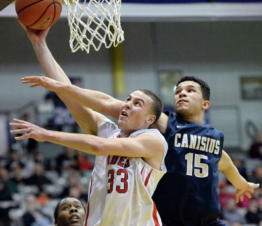 Albany Academy's #33 Steve Low, left, gets past Canisius' #15 Justin Jones to score during the Class A Boys' Federation Tournament final at the SEFCU Arena Saturday March 28, 2015 in Albany, NY.  (John Carl D'Annibale / Times Union) Photo: John Carl D'Annibale / 00031190A