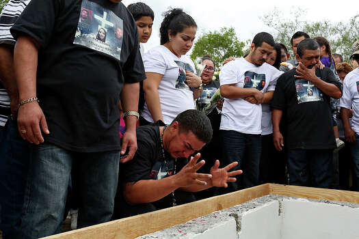 Juan Pablo Zapata grieves during the burial of his cousins, Erica Alvarado Rivera, 26, Alex Alvarado, 22, and Jose Angel Alvarado, 21, in El Control, Mexico on Sunday, November, 2, 2014. The siblings, U.S. Citizens from Progreso, were found shot to death more than two weeks after they went missing from a restaurant near El Control. At right are the siblings' oldest brother, Pete Alvarado, and their father, Pedro Alvarado. Photo: Lisa Krantz / Lisa Krantz / SAN ANTONIO EXPRESS-NEWS