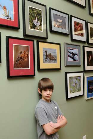 Birds are Joey Lounsbury, 13, of Danbury, CT, favorite subjects for his photography. Lounsbury poses with some of his photos that are on display at Birds Unlimited,  317 Federal Rd., Brookfield, CT on Wednesday, March 2, 2010. Photo: Jay Weir / The News-Times