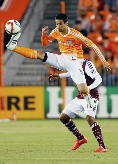 Dynamo defender Raul Rodriguez goes airborne to bring down the ball in front of Colorado's Gabriel Torres on Saturday night at BBVA Compass Stadium. Rodriguez started the game after missing the previous two matches. Photo: Scott Halleran, Staff / 2015 Getty Images