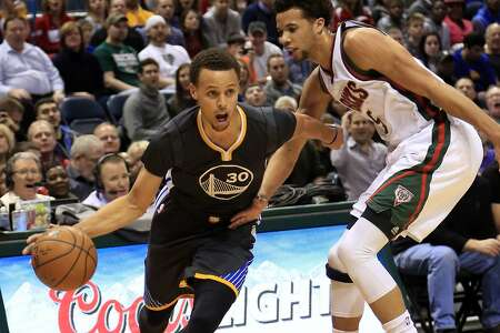 Golden State Warriors guard Stephen Curry, left, drives to the basket against Milwaukee Bucks guard Michael Carter-Williams during the first half of an NBA basketball game Saturday, March 28, 2015 in Milwaukee. (AP Photo/Darren Hauck)