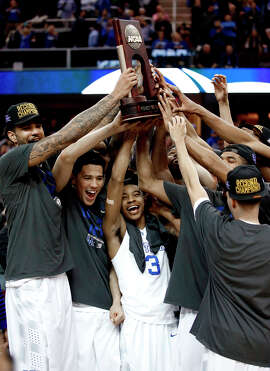Kentucky players hoist the trophy after defeating Notre Dame in the Midwest Regional Final.