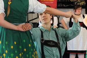 ZachBrown, of Deer Park kneels as he dances a traditional German dance with Amy Howell, of Pasadena, during the annual Tomball German Heritage Festival in downtown Tomball.