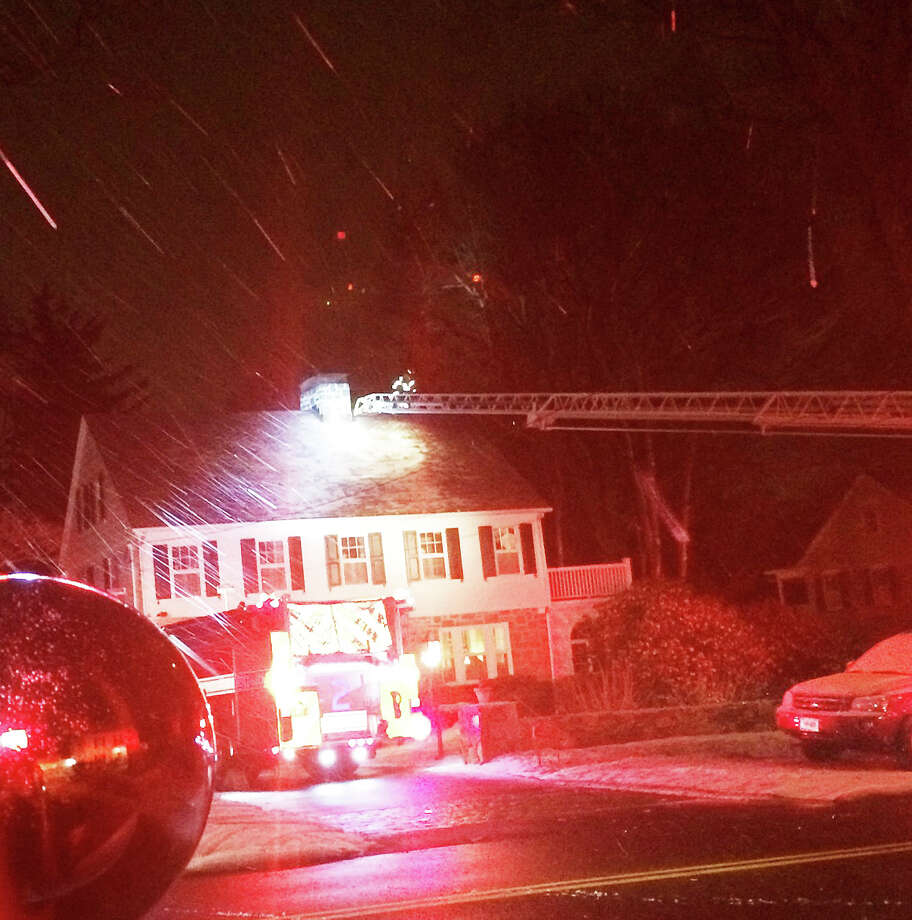 A ladder from an aerial truck is used by firefighters to gain access to a chimney fire reported Saturday night at a Toilsome Hill Road home. Photo: Fairfield Fire Department / Fairfield Citizen