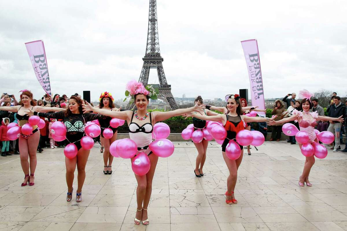 Women dance before throwing their bras up in the air during the 6th edition of the Pink Bra Bazaar Rally at Trocadero Square next to the Eiffel tower on March 29, 2015 in Paris, France. Pink Bra Bazaar is a charitable organization that aims to educate about breast health and supports women with breast cancer.