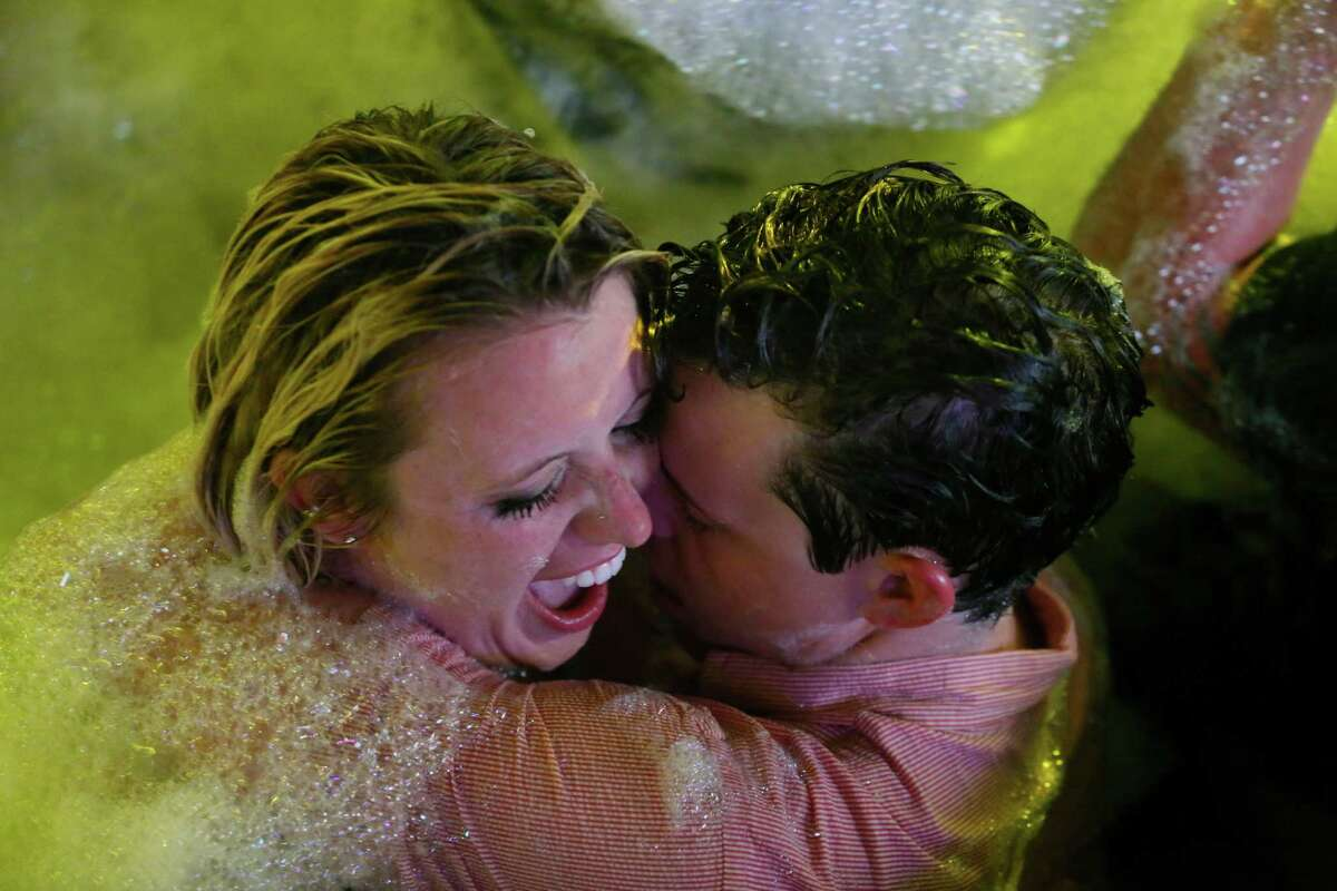 Spring Breakers embrace during a foam bath party at The City nightclub in the Caribbean resort city of Cancun, Mexico, early Monday, March 16, 2015. Cancun continues to be one of the top foreign destination for U.S. college students to travel to for Spring Break.