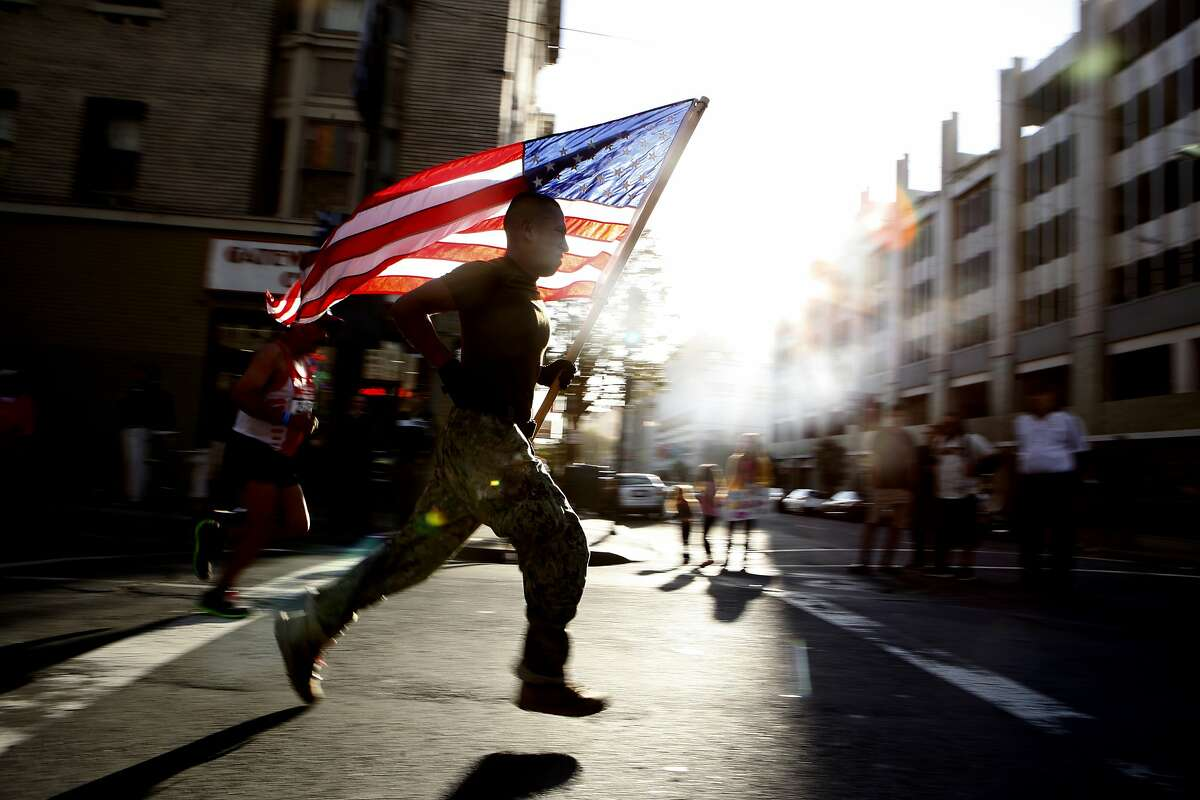 A man in military uniform brandished an American flag as he ran the final stretch of the Rock 'n' Roll Half Marathon, Sunday, March 29, 2015, in San Francisco, Calif.