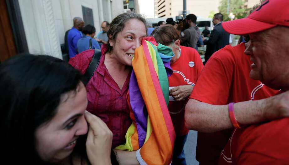 Julie Pousson (center) wipes away tears as she celebrates after a nondiscrimination ordinance was passed by the San Antonio City Council in 2013. There are fears that a bill in the Legislature would pre-empt such legislation if they disagree with state law. Photo: Associated Press File Photo / AP