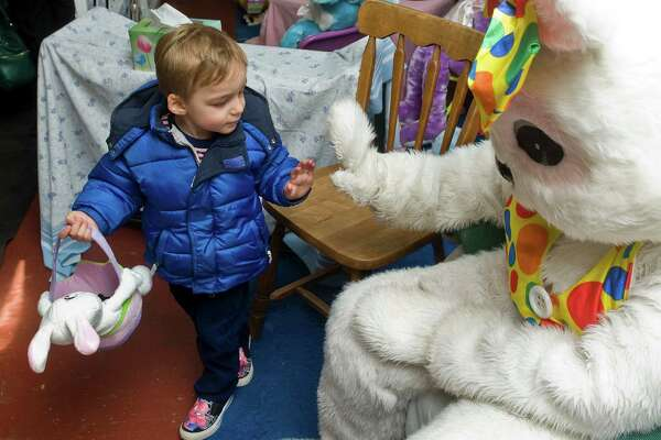 Two-year-old John Michael Quis gives the Easter Bunny a high-five after a short ride in the Danbury Railway Museum train yard. Sunday, March 29, 2015