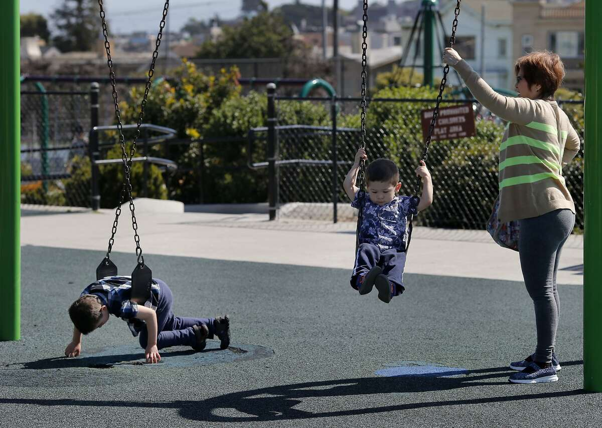 Tracey Bullock's six year old boy with autism (left) spins in his swing while the boy's brother and grandmother Lynda Chew play at Balboa Park Sunday March 29, 2015.