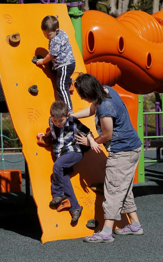Tracey Bullock (right) helps her six year old autistic son down from a climbing play structure while her three year old watches at Balboa Park Sunday March 29, 2015 in San Francisco, Calif.  Photo: Brant Ward, The Chronicle