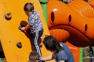 Tracey Bullock (right) helps her six year old autistic son down from a climbing play structure while her three year old watches at Balboa Park Sunday March 29, 2015 in San Francisco, Calif. Kaiser is launching one of the largest genetic research studies on autism ever attempted. Tracey Bullock, her husband and six year old boy with autism plan to participate in the study.