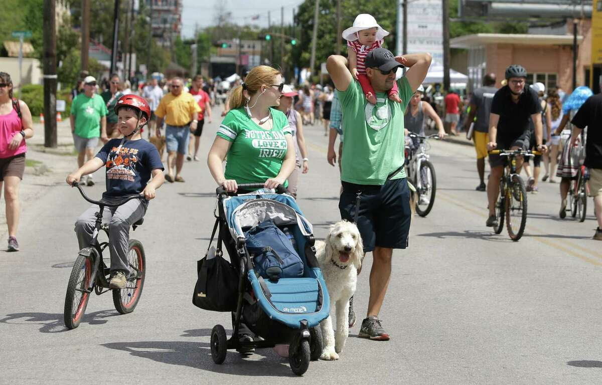 Maggie Mendoza, left, of Houston and Carlhos Mendoza, right, walk with their daughter, Isabel, 9-months-old and dog, Parker, along Westheimer during the Cigna Sunday Streets Sunday, March 29, 2015, in Houston. Part bike tour, part walking tour, part block party, Cigna Sunday Streets was created to promote and improve the health of Houstonians and offers new economic opportunities for neighborhood commercial districts.