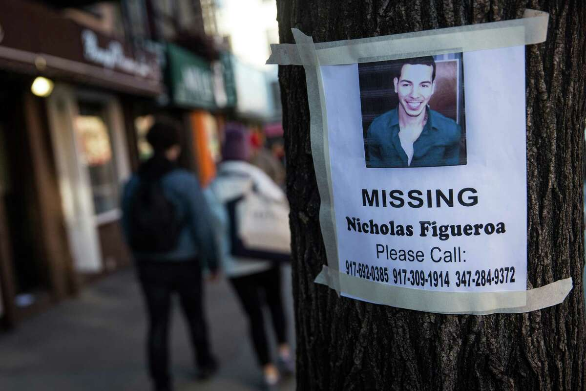 A sign for Nicholas Figeroa was posted on a tree near the site of a building explosion. Family members said his body was pulled from the rubble Sunday.