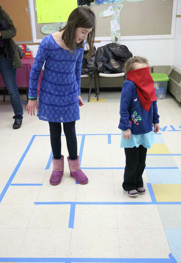 Rachel Logue age 10 of Fairfield guides Macey Greene age 5 also of Fairfield through a blind folded maze during Sunday's Pre-Passover family fun at Model Matzah event at Chabad of Fairfield Photo: Mike Ross / Mike Ross Connecticut Post freelance - @www.mikerossphoto.com
